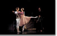 Photo of Igor Vassin as Romeo and Maria Mosina as Juliet, and, in the background, Gregory K. Gonzales as Friar Lawrence.