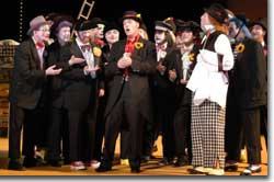 Photo of Count Almaviva (John Tessier), Fiorello (Bradley Thompson) and the Opera Colorado Chorus.
