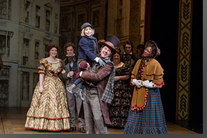 (Left to right) Fred's Wife (Grace Morgan), Fred (Jim Poulous), Tiny Tim (Peyton Goossen), Bob Cratchit (Brian Vaughn), and Mrs. Cratchit (Latoya Cameron)