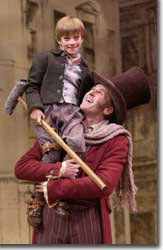 Photo of Harrison Steele as Tiny Tim and Sam Gregory as Bob Cratchit