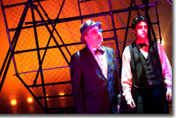 (Left to right) Dan O'Neill as joseph k and Josh Hartwell as Kafka in front of the relentless wheel