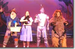 Photo of Scott Beyette as the Scarecrow, Emily Van Fleet as Dorothy, Lyric as Toto, John Scott Clough as the Tin Man, and A.K. Klimpke as the Lion
